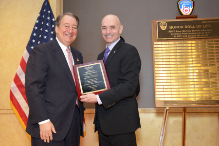 Howard Milstein and Commissioner Salvatore Cassano. Commissioner Cassano is holding a plaque recognizing his role in promoting donations of blood and bone marrow during his time as FDNY commissioner.